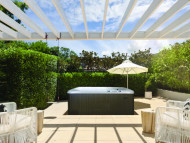 Beachcomber spa with pergola and privacy bushes