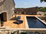 Stunning rectangular swimming pool with wood deck and stone accents
