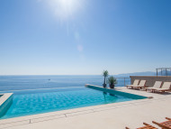 Overflowing swimming pool with vanishing edge and ocean view