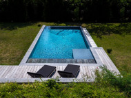 In-ground rectangular swimming pool with integrated bench