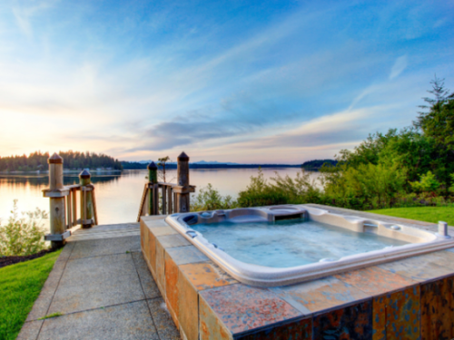 Outdoor hot tub with view over lake and mountains
